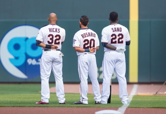 Jul 6, 2015; Minneapolis, MN, USA; Minnesota Twins center fielder Aaron Hicks (32), left fielder Eddie Rosario (20) and designated hitter Miguel Sano (22) stand during the national anthem against the Baltimore Orioles at Target Field. Mandatory Credit: Brad Rempel-USA TODAY Sports